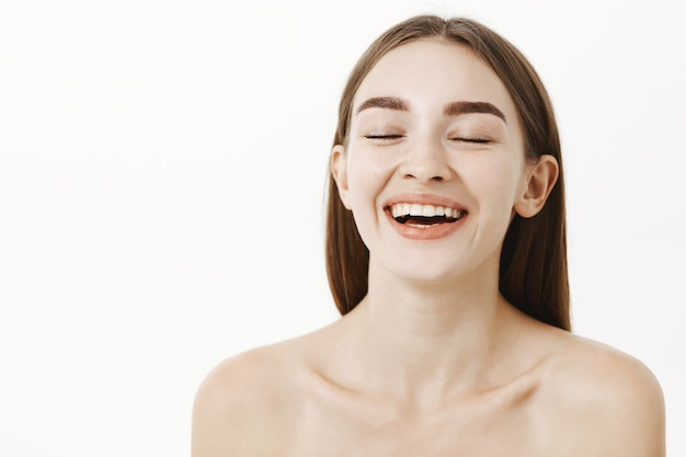 Delighted charming young and beautiful woman closing eyes and smiling from pleasure and satisfaction posing naked enjoying cosmetology procedure
