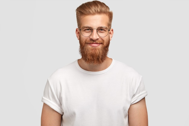 Delighted cheerful fashionable hispster with ginger beard, wears round spectacles and white t shirt