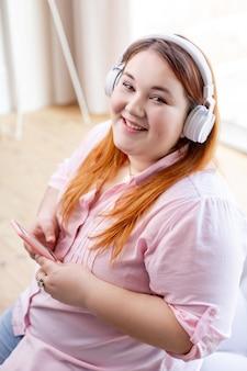 Довольная жизнерадостная женщина сидит со своим смартфоном во время прослушивания музыки
