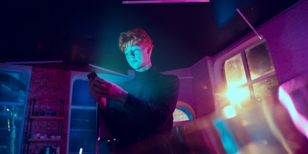 아주 기뻐하는. 네온 조명이 켜진 실내에서 세련된 빨강머리 남자의 영화적 초상화. 보라색 - 파란색의 영화 효과처럼 톤. 실내에서 화려한 조명으로 스마트폰을 사용하는 백인 모델입니다. 전단.