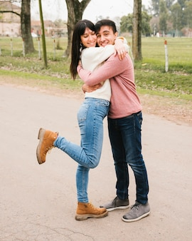 Delighted couple standing on asphalt and hugging