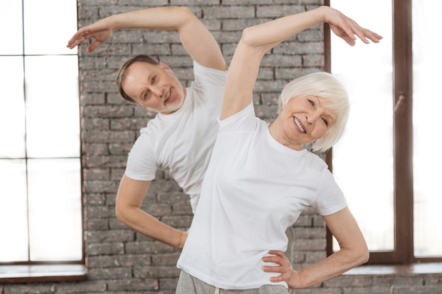 Счастливая пара в белых футболках, держась за талию за руки, сохраняя улыбку на лице