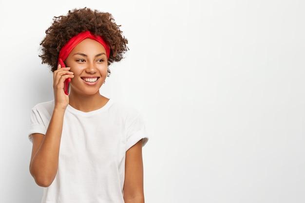 Обрадованная кудрявая афро-женщина держит мобильный телефон возле уха, наслаждается приятной беседой, позитивно улыбается