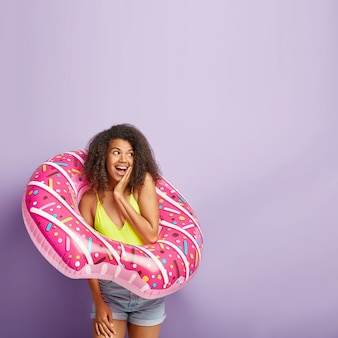 喜んでいる巻き毛の女の子は夏休みを夢見ています