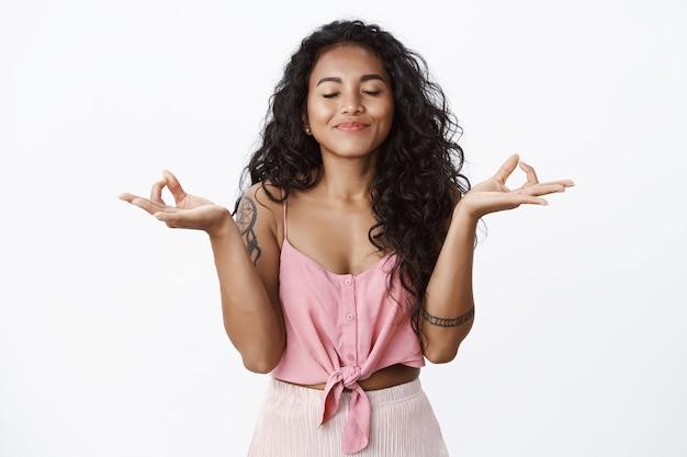 Felice ragazza dai capelli ricci con tatuaggi che meditano, alza le mani nel gesto zen, pratica lo yoga, chiudi gli occhi e sorride felice, inspira aria fresca, calmati sollevato, muro bianco