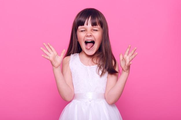 행복하게 비명을 지르는 흰 드레스를 입고 기뻐하는 귀여운 여자 아이, 닫힌 눈과 넓게 열린 입으로 고함, 놀라움, 분홍색 벽 위에 절연
