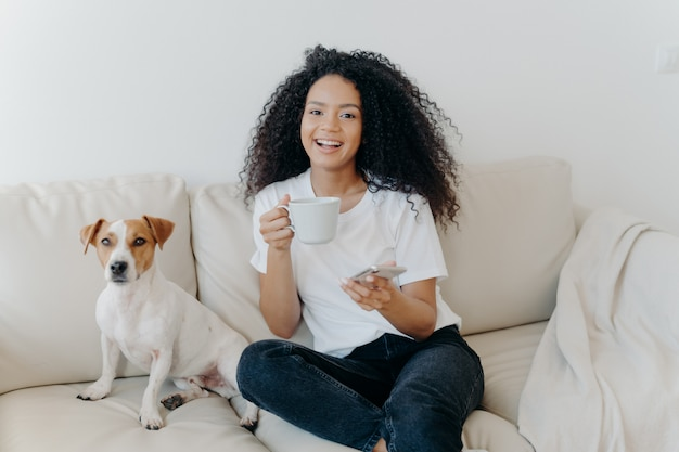 Delighted dark skinned woman poses in modern apartment, sits on comfortable sofa with pet, drinks coffee, uses mobile phone for online communication, being in good mood, flipping news, uses app