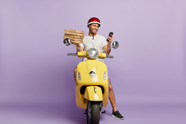 Delighted deliveryman driving scooter while holding pizza boxes