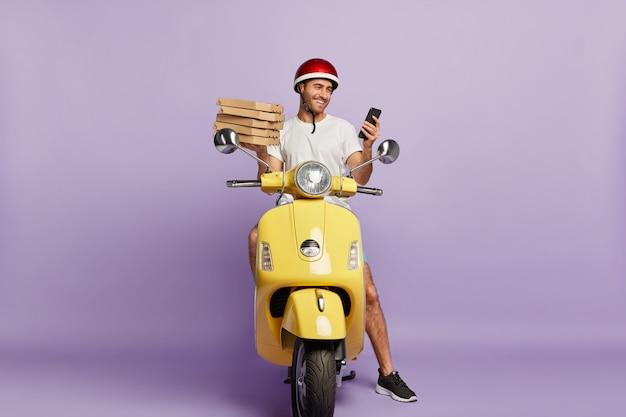 Felice fattorino alla guida di uno scooter tenendo in mano scatole per pizza