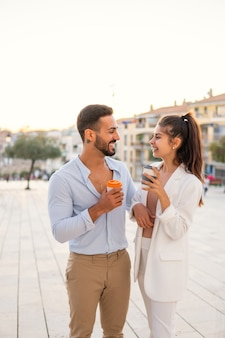 Delighted ethnic couple with coffee to go in evening city