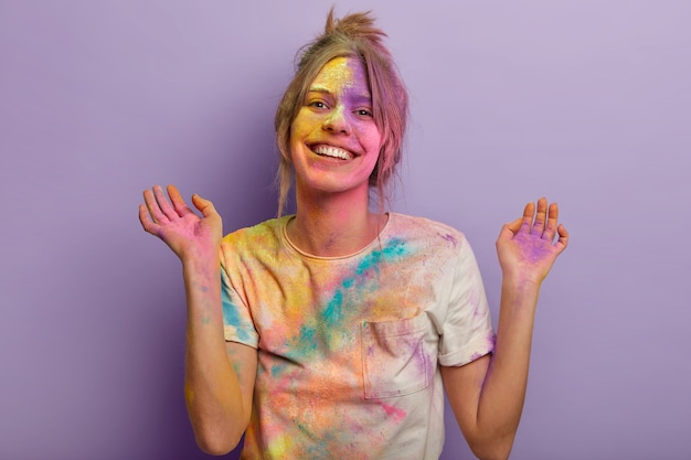 Delighted european woman with carefree expression, raises hands, smeared with colorful dyes, wears white t shirt, smiles gladfully, celebrates holi fest, paint party isolated over purple wall.