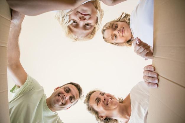Счастливая семья с милыми детьми, открывающая движущуюся картонную коробку и заглядывающая внутрь