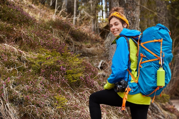 Delighted female camper carries backpack, professional camera