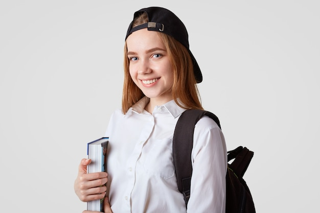 Delighted female student holds thick book, wears fashionable black cap, smiles gladfully, isolated on white. adorable cute schoolgirl with rucksack happy to finish school