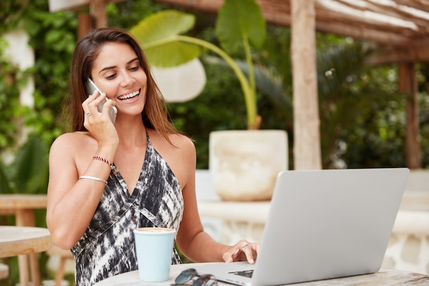 Delighted female watches interesting webinar on portable laptop computer, receives call from friend, enjoys free time in cafe interior, recreate in resort hot country. people, communication, lifestyle
