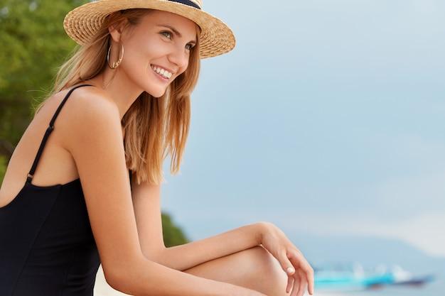 Обрадованная самка с радостным выражением лица задумчиво смотрит вдаль, мечтает о рае, сидит на фоне голубого неба, дышит свежим морским воздухом. счастливый турист женщины отдыхает на береговой линии