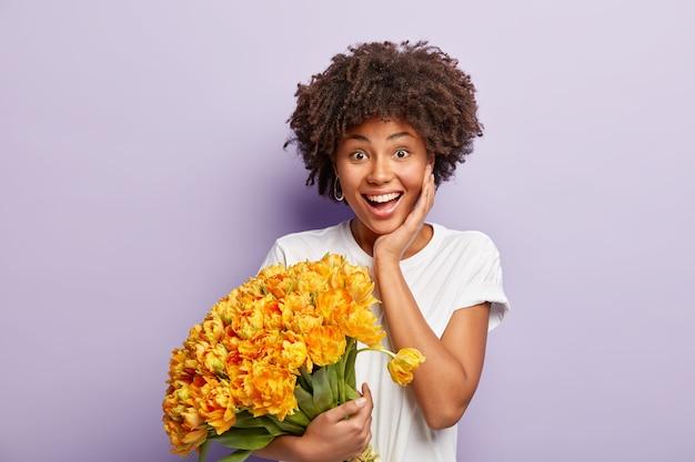 이빨 미소, 선명한 머리카락, 남자 친구로부터 행복한 제안을받은 기쁘게 여성은 보라색 벽에 고립 된 노란색 꽃의 멋진 꽃다발을 보유하고 있습니다. 긍정적 인 감정과 감정 개념