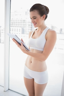 Delighted fit brown haired model in sportswear looking at a tablet pc
