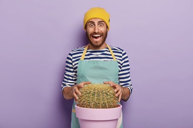 大きな鉢植えのサボテンでポーズをとる喜んでいる庭師