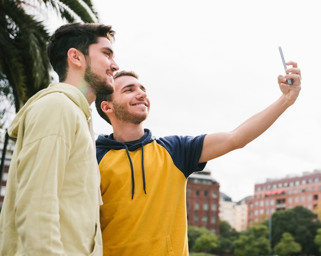 Delighted gay couple shooting selfie on street