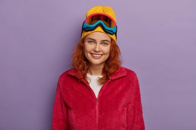 매력적인 외모를 가진 기쁘게 생강 여자, 노란 모자와 빨간 부드러운 재킷을 입고, 얼굴에 즐거운 미소를 가지고 있으며, 보라색 배경 위에 고립 된 카메라를 직접 바라 봅니다.