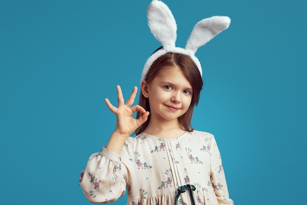 Довольная девушка с кроличьими ушками и показывающим знаком на синей стене
