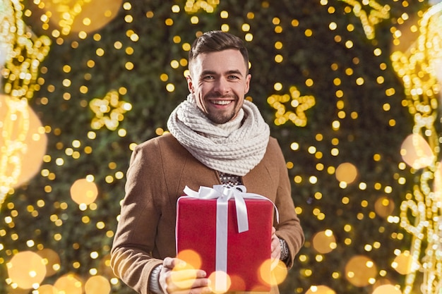 Delighted guy with present smiling and looking while standing against christmas tree with fairy lights