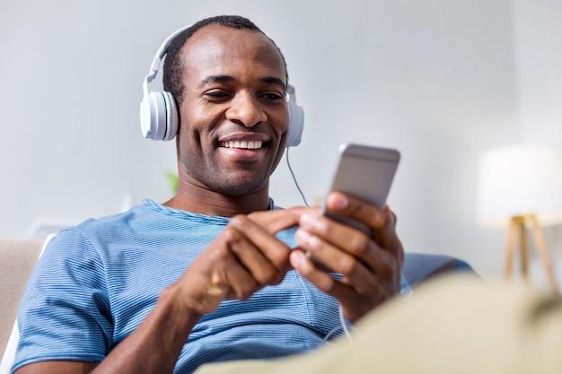 Довольный счастливый позитивный мужчина в наушниках и слушает музыку во время использования своего смартфона