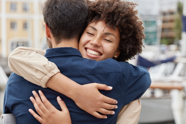 Delighted happy smiling african american woman says goodbye to boyfriend, gives warm hug
