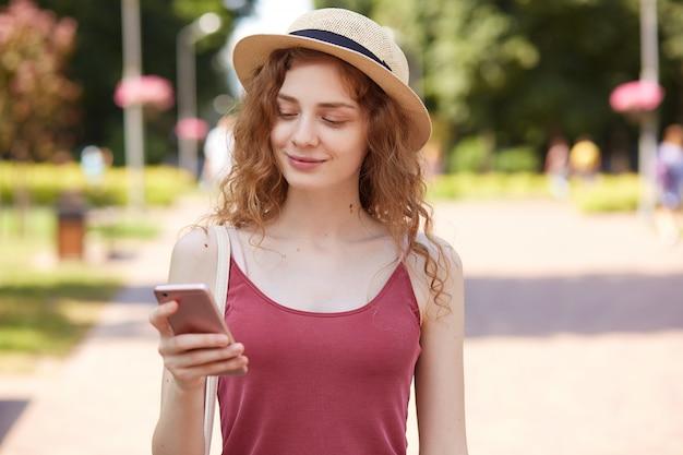 楽しい表情で喜んで幸せな若い女性、誠実に笑顔、ニュースを読んで、スマートフォンを持って