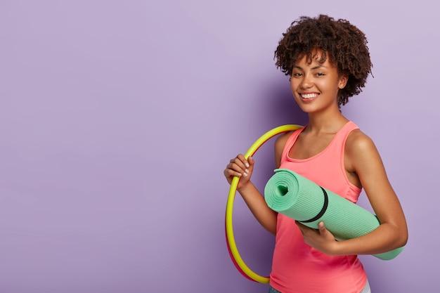 기뻐하는 건강한 여성이 후프를 회전하고, 카레 마트를 운반하며, 훈련을 받고, 건강한 라이프 스타일을이 끕니다.