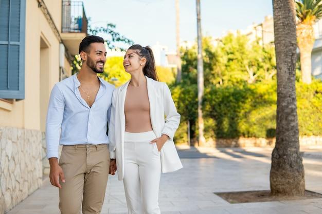 街の通りを一緒に歩いて喜んでヒスパニック系のカップル