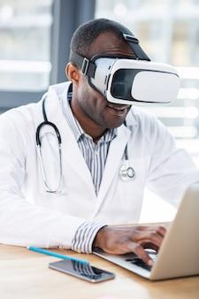 Довольный международный ученый в маске виртуальной реальности, использующей ее в технологических исследованиях