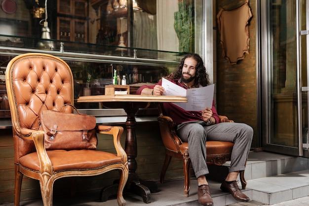 Довольный радостный человек сидит за столом во время чтения меню