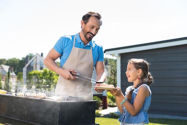 그의 딸 접시에 음식을 넣는 동안 웃 고 기쁘게 즐거운 남자