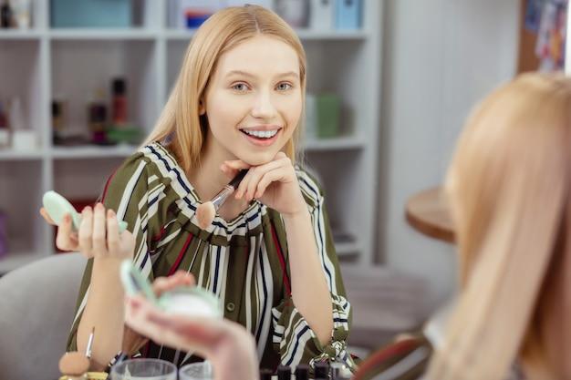 素晴らしい気分になりながら彼女の反射に微笑んで喜んでうれしそうな女性