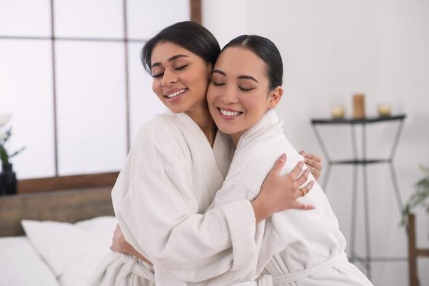 抱き合って目を閉じて喜ぶうれしそうな女性たち