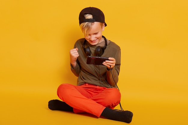 Delighted little boy dresses orange trousers and green shirt playing video game on cellphone and clenching fist while sitting on floor with crossed legs isolated on yellow
