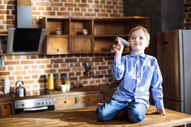 紙飛行機で遊んでいる間、台所に座って喜んでいる小さな男の子