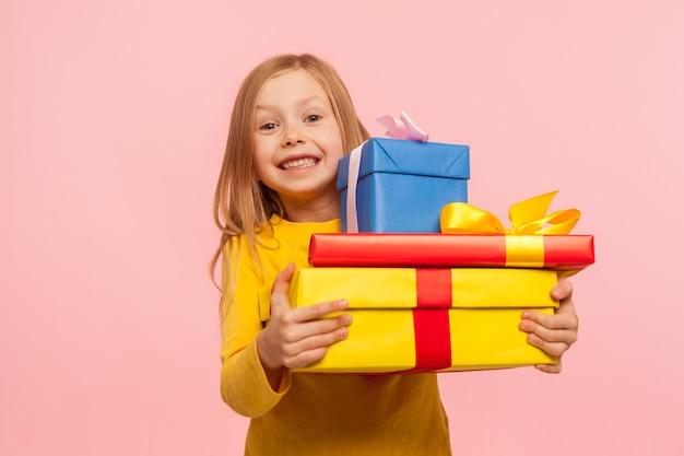 많은 선물 상자를 껴안고 진심 어린 행복의 표정으로 카메라를 보며 웃고 있는 어린 소녀, 많은 선물로 완벽한 생일을 즐기고 있습니다. 실내 스튜디오 촬영, 분홍색 배경