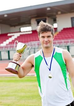 Восхищенный мужской спортсмен с чашкой и медалью