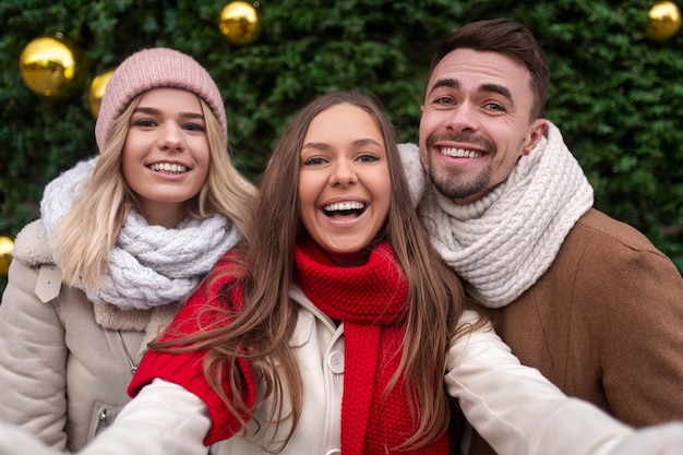 Delighted male and female friends in outerwear smiling and looking while taking selfie near coniferous tree on christmas day