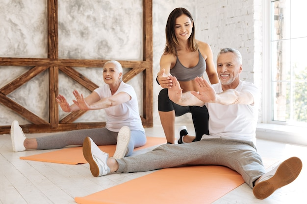 Delighted male person sitting on the rug and keeping smile on his face while stretching his legs