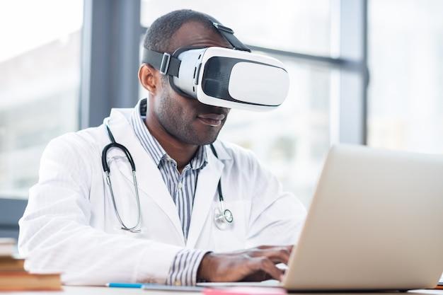 Довольный мужчина в маске vr, глядя на экран своего ноутбука