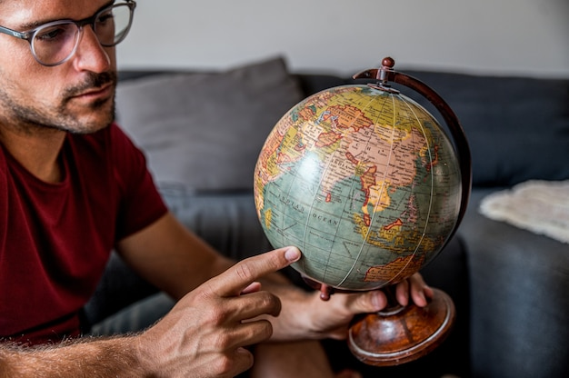 Delighted male traveler choosing country on planet earth globe before adventure while sitting in room with suitcase