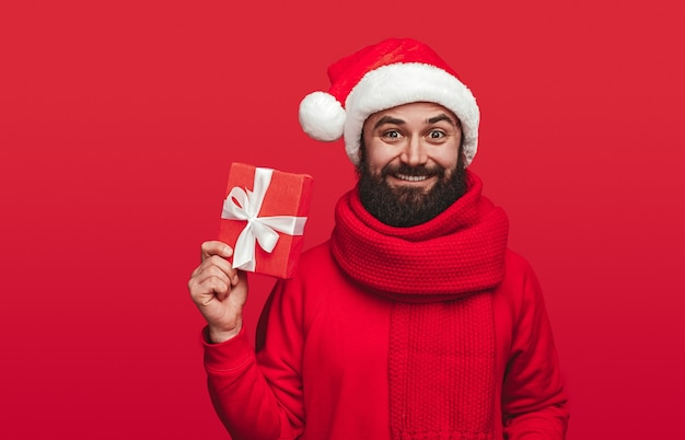 Delighted male wearing santa hat and knitted scarf