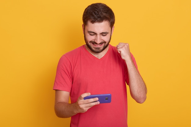 Delighted man dresses red casual t-shirt playing video game on cellphone and clenching fist isolated over yellow studio