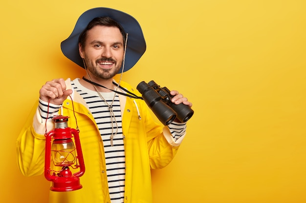 Delighted man with stubble, wears headgear and yellow raincoat, carries kerosene lamp and binoculars, looks gladfully at camera, stands indoor