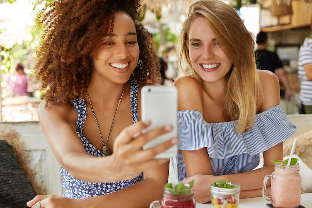 Delighted mixed race female models have fun together, pose for making selfie in smart phone, have broad pleasant smiles, pose at cafe with smoothie and cocktails. people, ethnicity and leisure