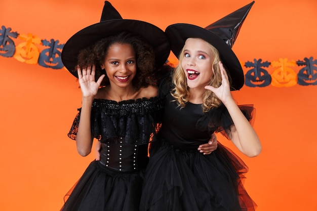 Delighted multinational girls in black halloween costumes hugging and listening isolated over orange pumpkin wall